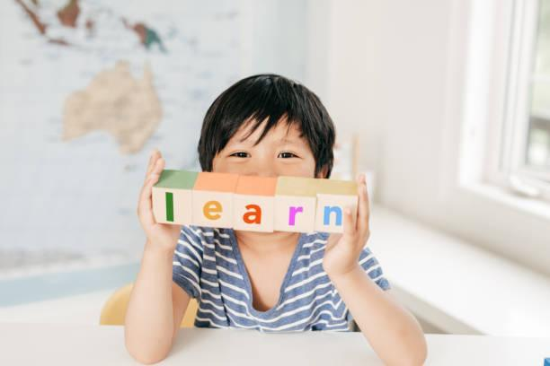 Boy holding up wooden blocks spelling LEARN