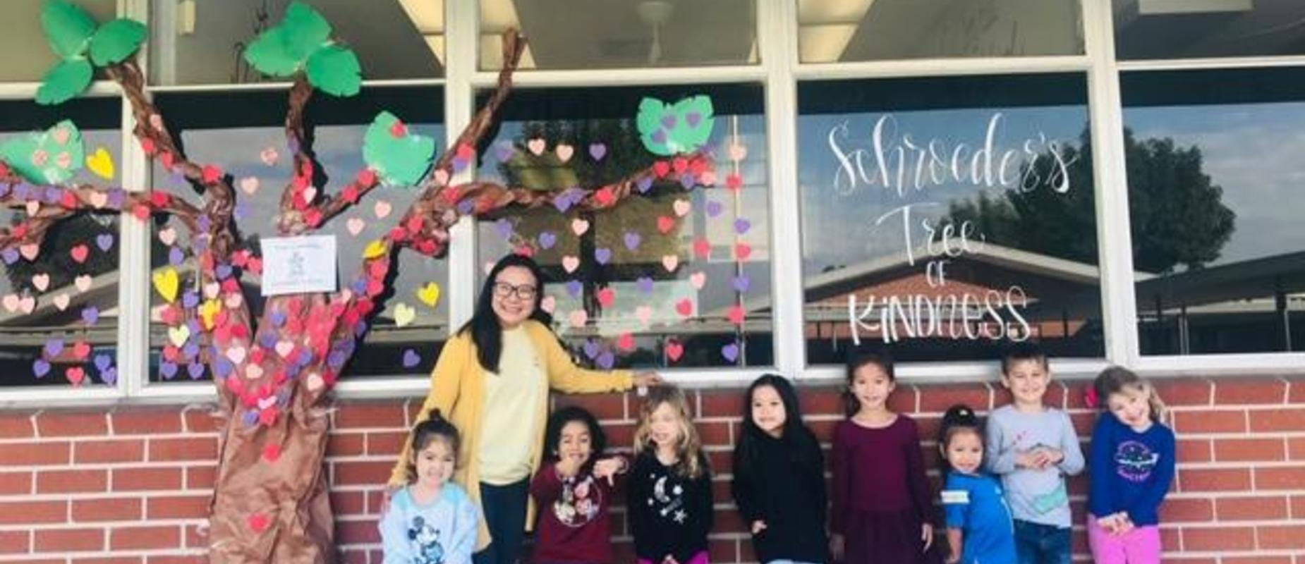 students stand in front of Tree of Kindness