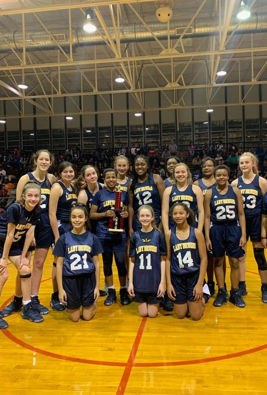 Group of young girls in basketball uniforms surrounding trophy, smiling