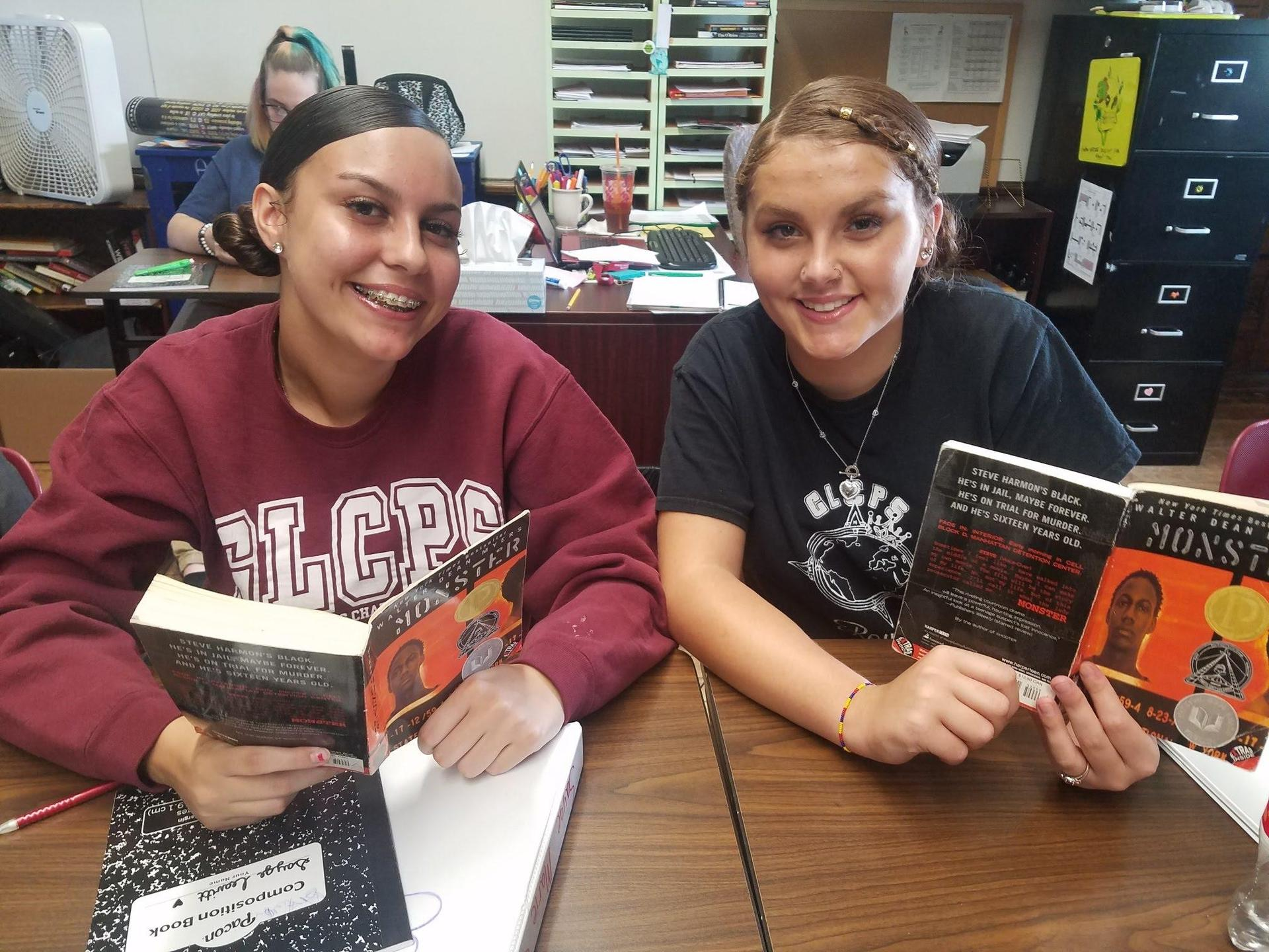 Two students reading and smiling.