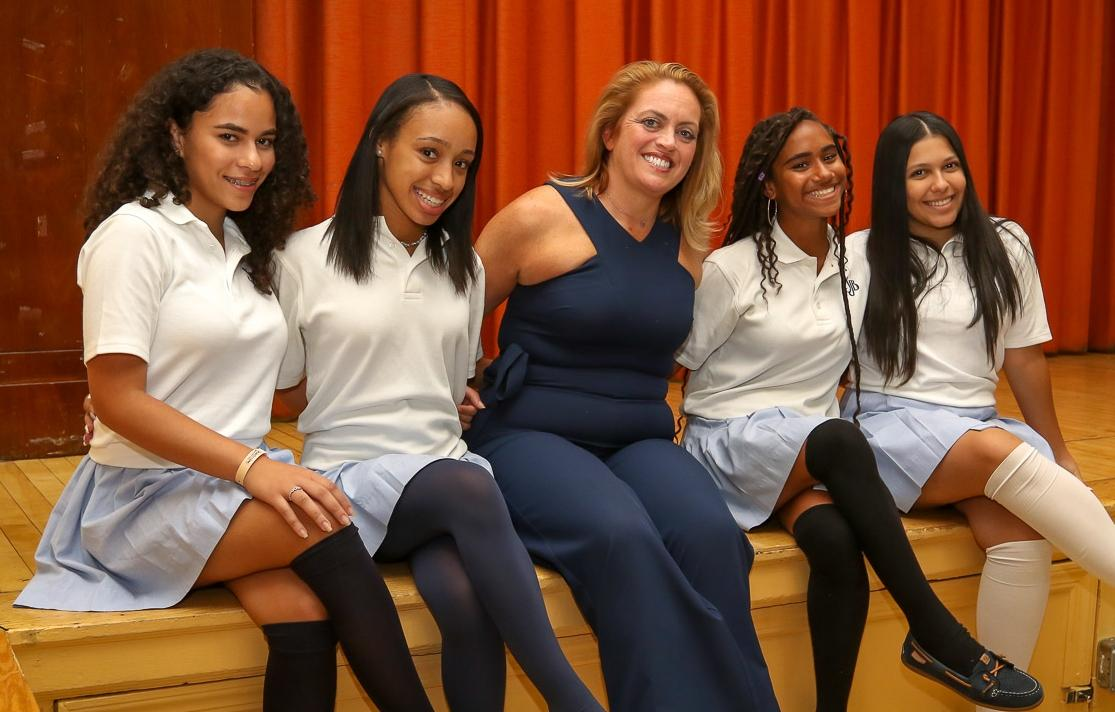 High school girls in white shirts and blue skirts sit on a stage with Dr. Guerriero in the middle wearing a navy blue jumpsuit