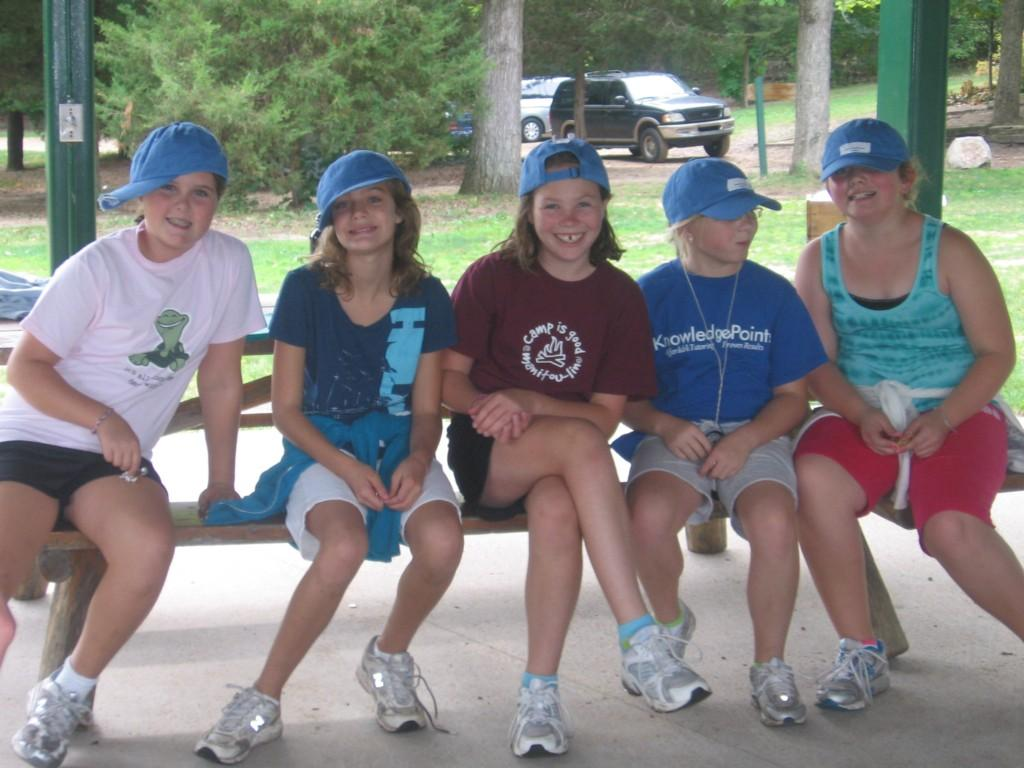 five girls pose on bench at camp
