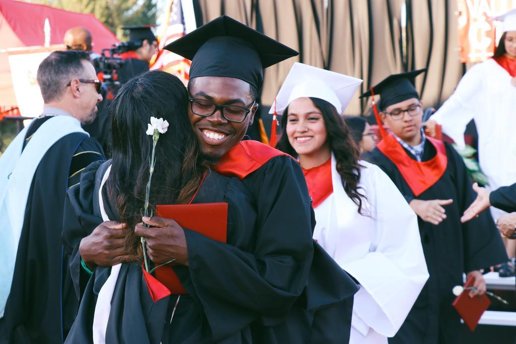 Class of 2019 graduate hugs Principal Karen Johnson