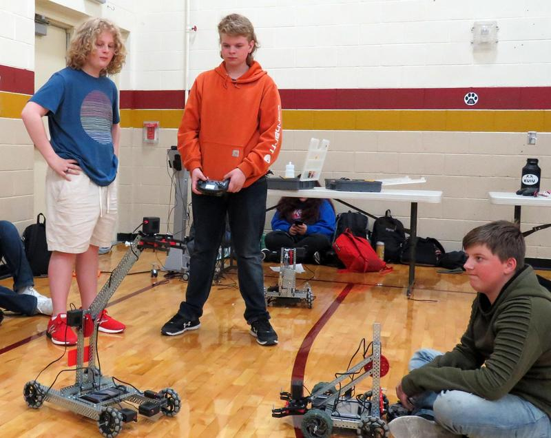 Two boys stand and one sits as they operate two small robots on the gym floor at East Valley.