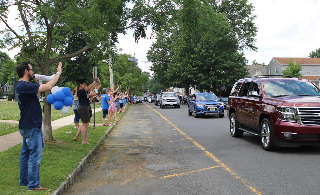 Photo of McKinley principal and staff waving to 5th graders passing by during Grade 5 Clap Out Car Parade