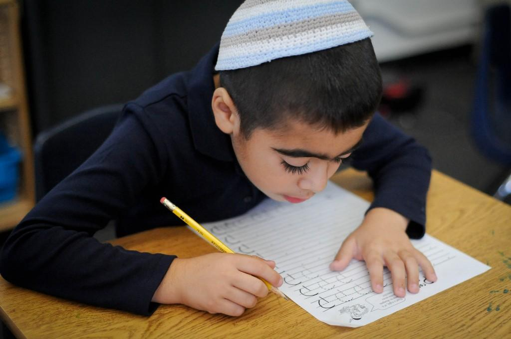 boy practicing writing hebrew letters