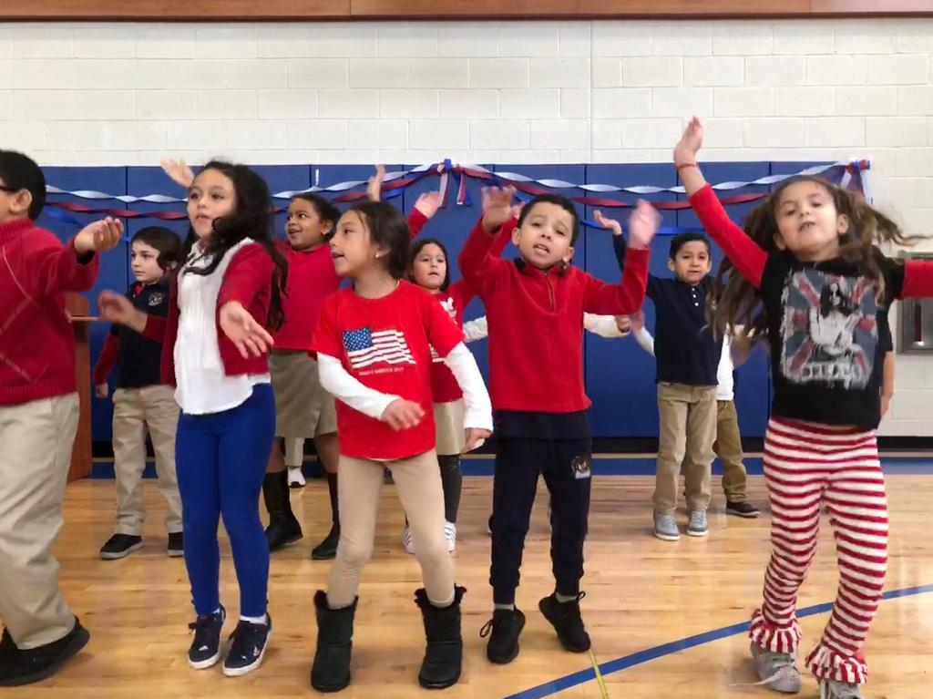 group of children proudly dancing for the veterans