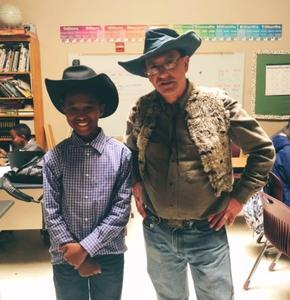 One male middle school student and one male teacher dressed up as cowboys.