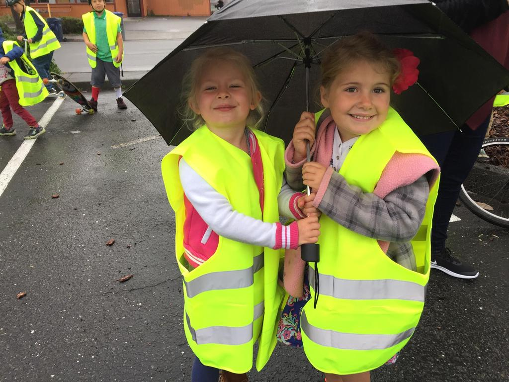 two girls smiling under an umbrella
