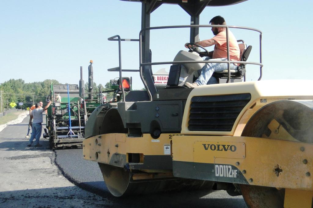This picture shows a vibratory roller compacting and smoothing newly laid top coat pavement on the main campus bus loop.