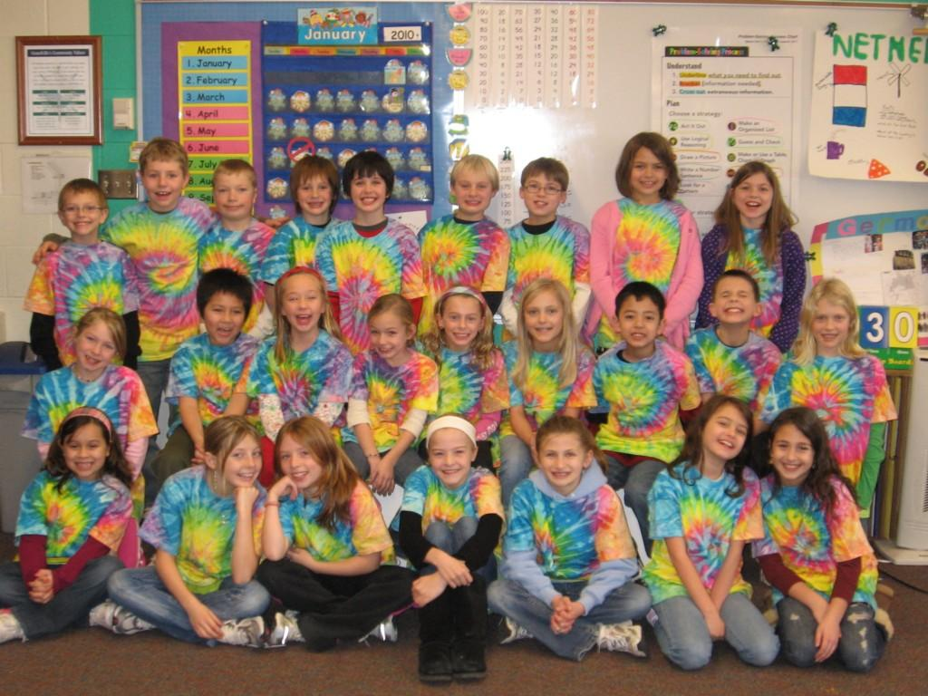 students in tie dye shirts smile at camera