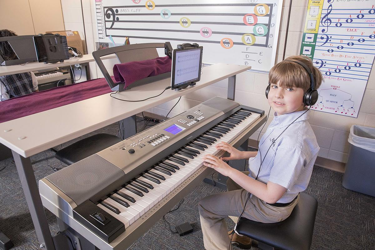 elementary boy in piano keyboarding class