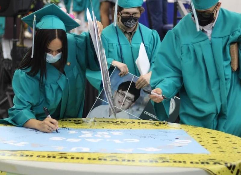 3 students in teal graduation gowns sign a card