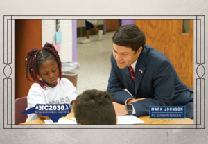 State Superintendent, Mark Johnson, works with two students in class
