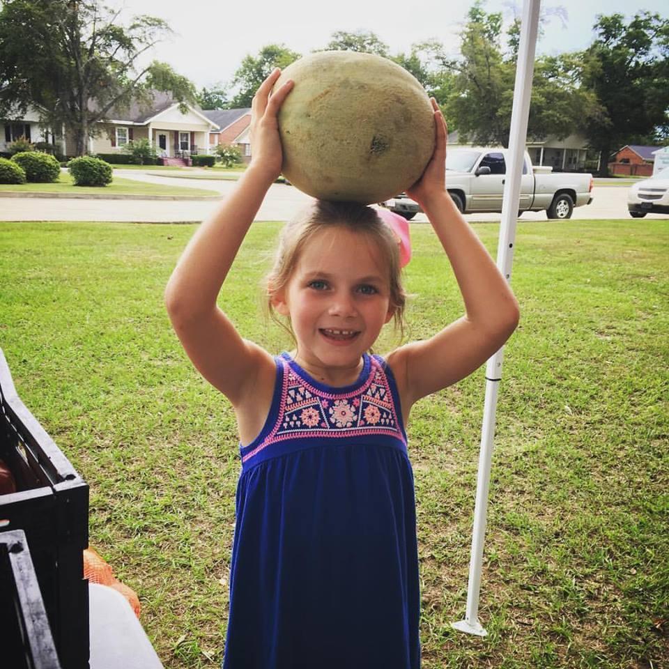 Girl holding a cantaloupe