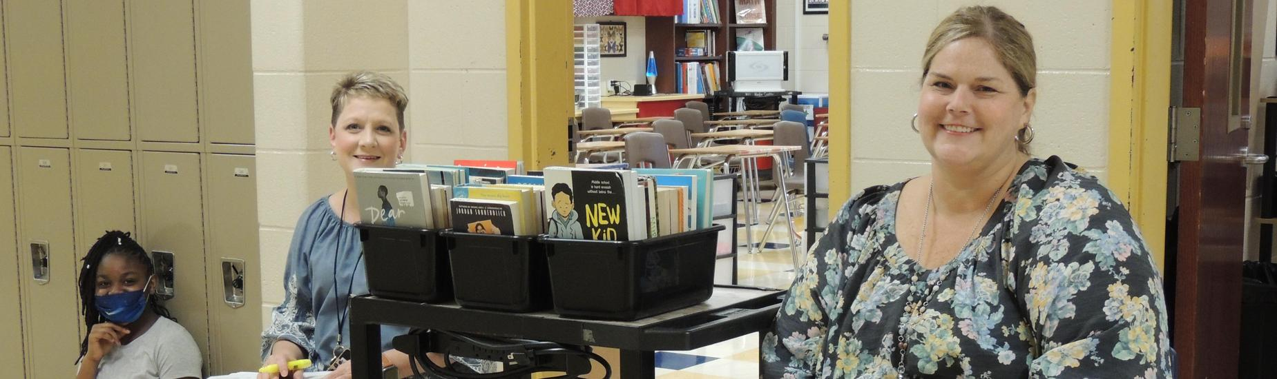 Mrs. Cook and Ms. Lewis in the hallway with books