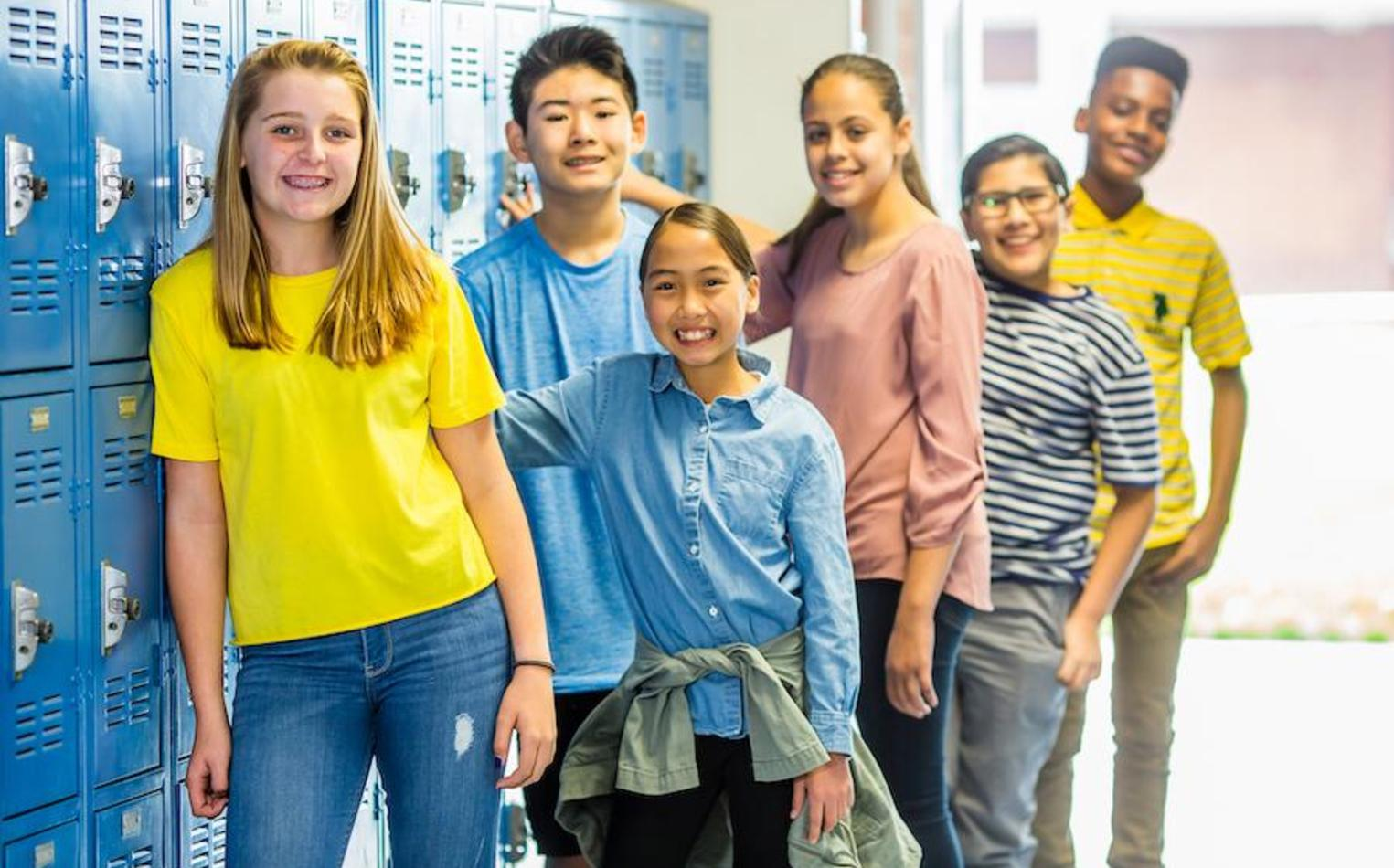 Middle school students hanging out near lockers.