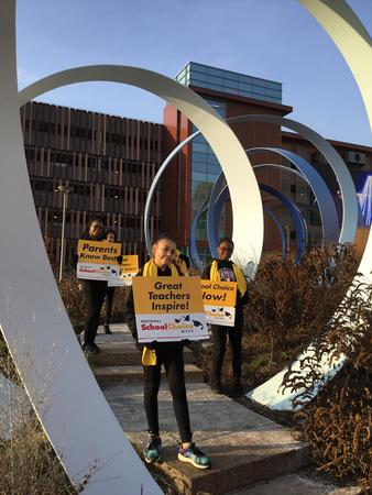 Picture of NSCW dancers holding School Choice signs.