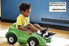 "Image of a young laughing child in a toy car. Quote: ""Having fun is the best way to learn."" - Albert Einstein"