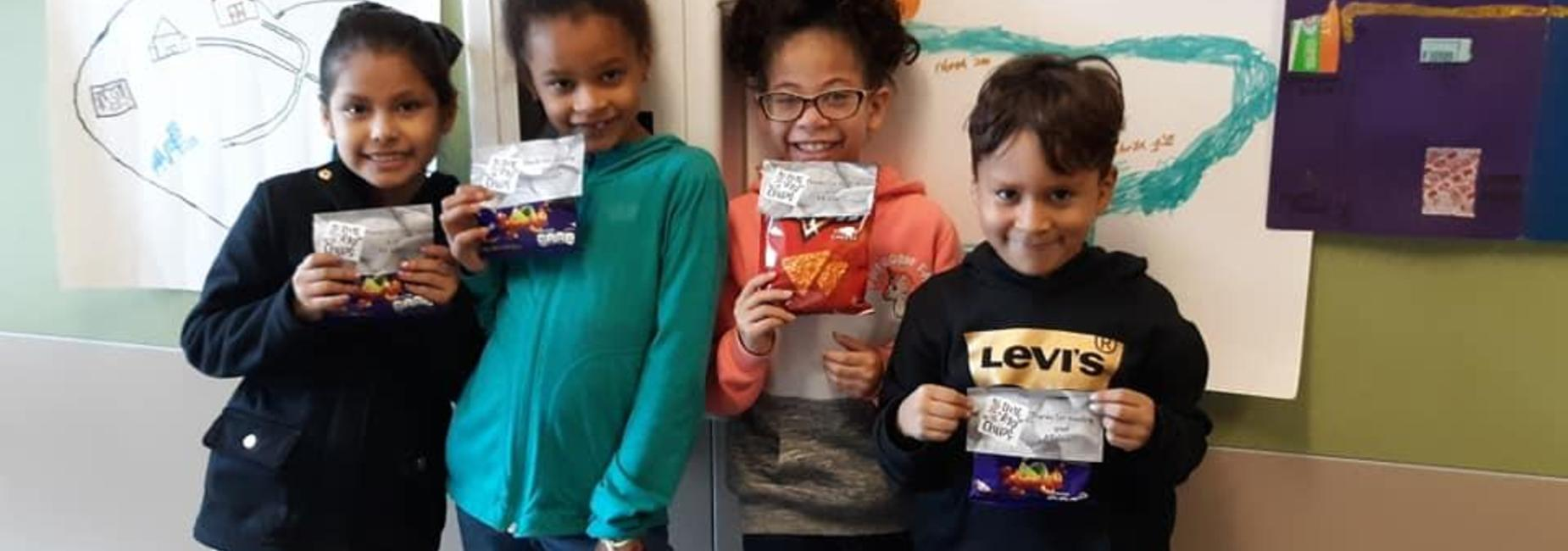 kids with chip bags for reading