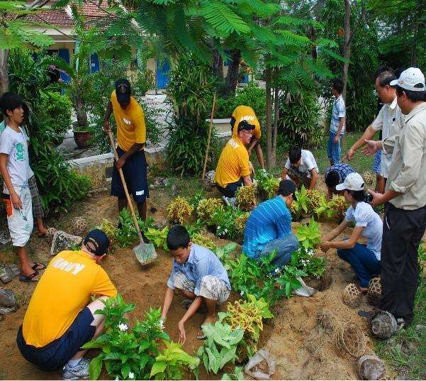 people in a community working to clean up a garden