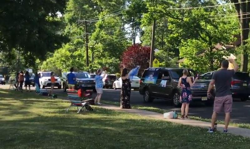 Photo of Jefferson teachers lined up and applauding 5th graders as they go by in their cars.
