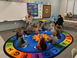 preschool students hear a book from a touring freshman