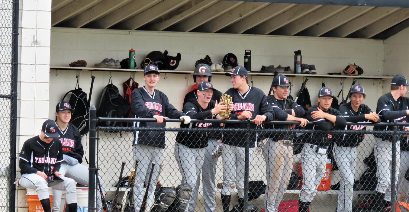 TK baseball team members watch from the dugout.