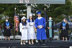 Triplets dressed in white and blue gowns pose after receiving their diplomas