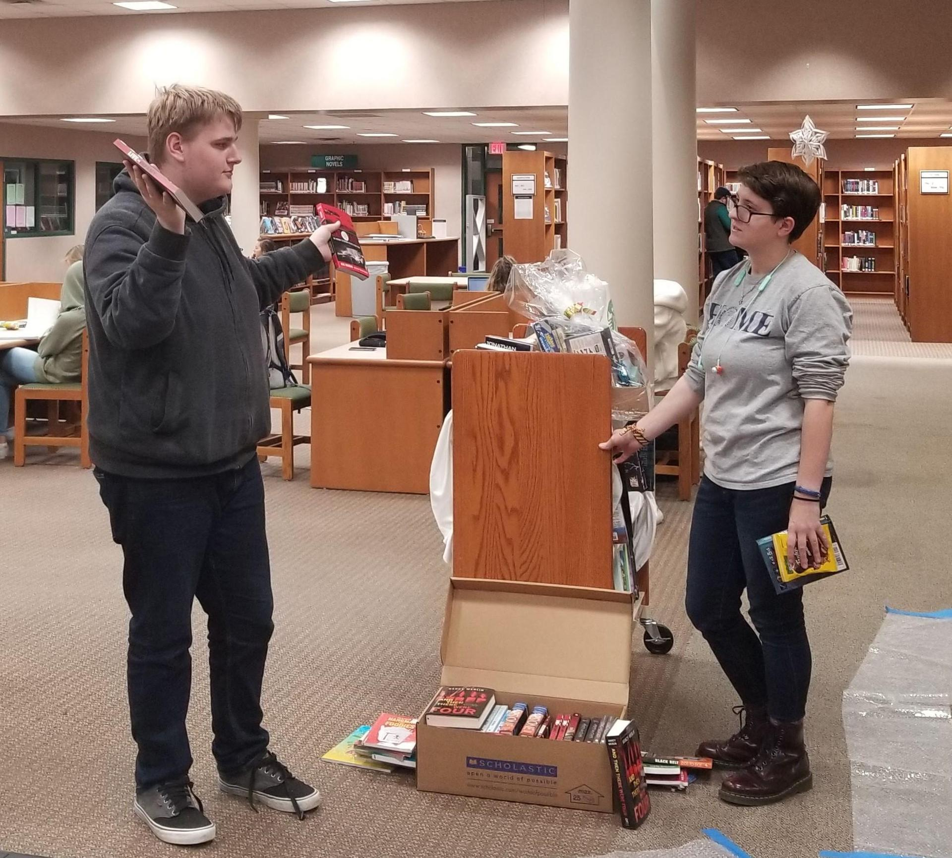 A male student holds up two books while talking to a female student who is holding one book