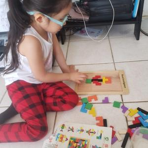 girl with glasses on the floor with puzzle pieces