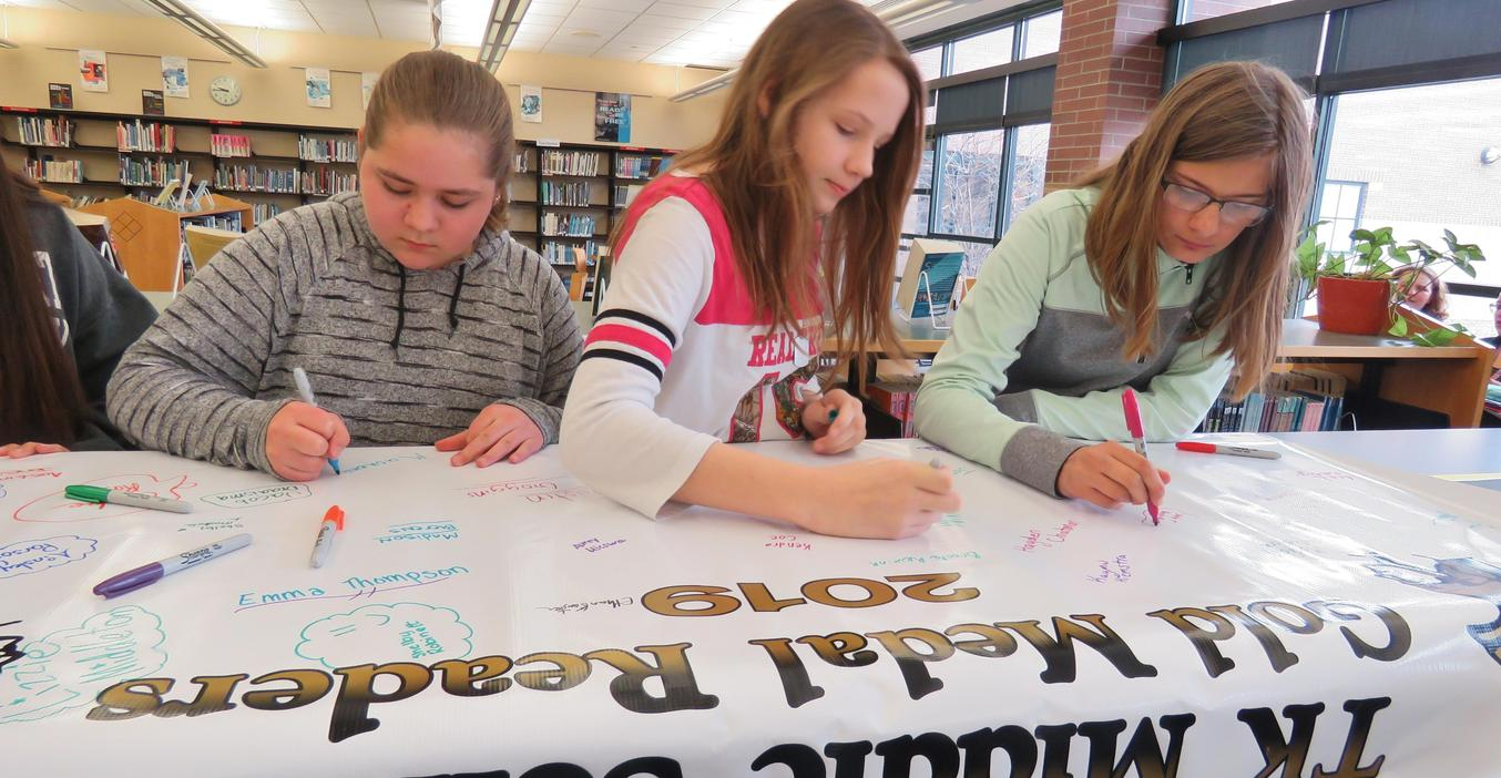 Students sign the Gold Medal Readers banner.