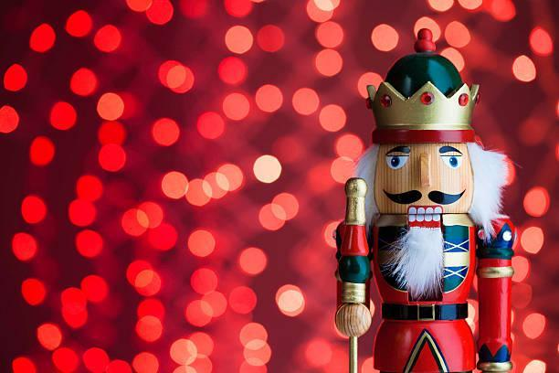 Red Nutcracker figure on right with red background with sparkles falling.