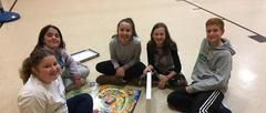Students smiling playing a board game sitting on gymnasium floor