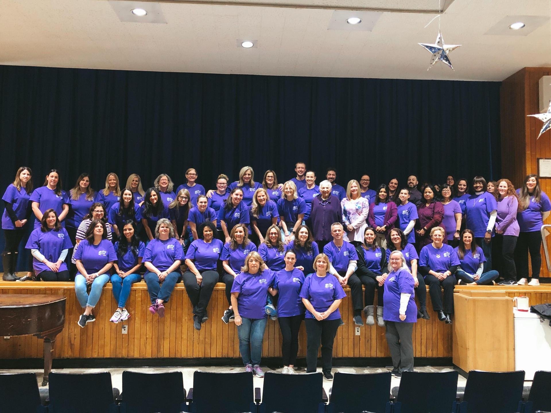 Teachers dressed in purple for PS I Love You Day all on stage