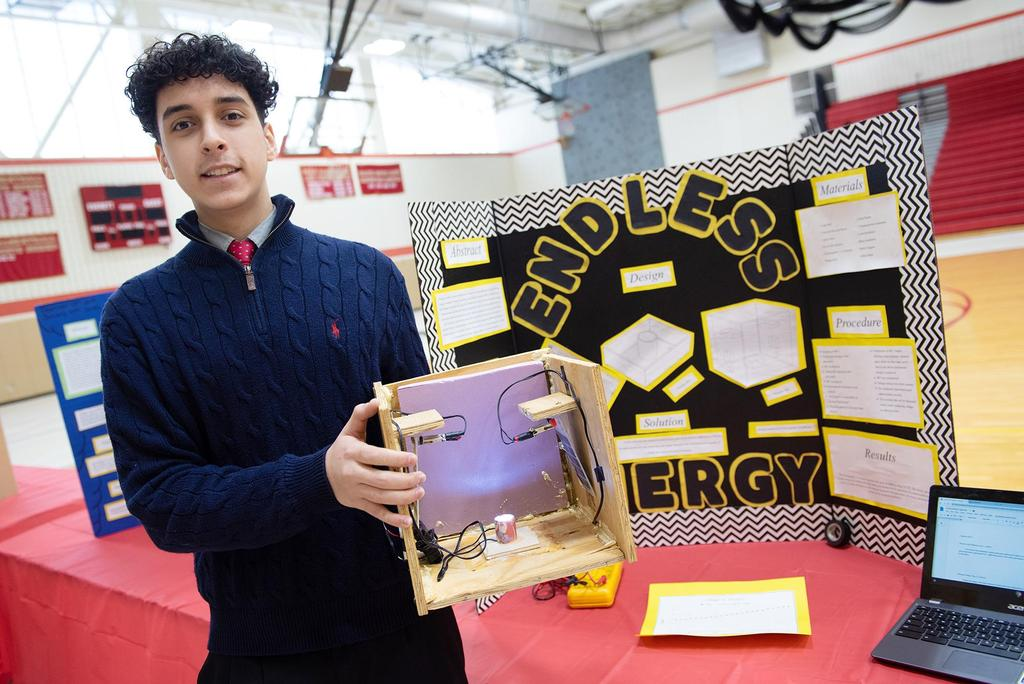 A student holds up his project called Endless Energy