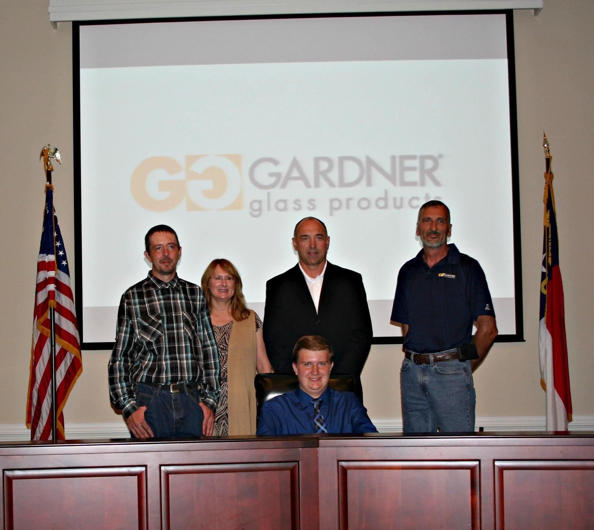 Tate Foster poses with his family in the Board Room during apprenticeship signing.