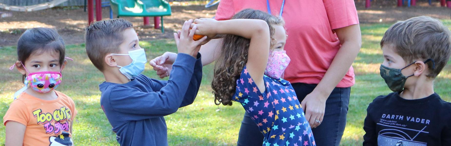 Photo of kindergartners passing small pumpkin as part of a game during annual Pumpkin Patch festivities