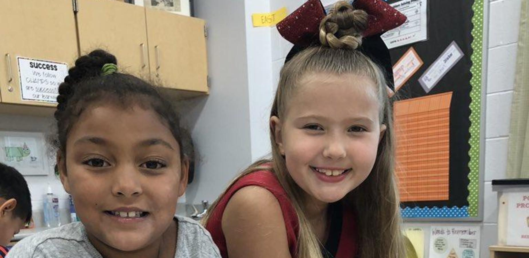 Photo of two girls at Compass Elementary who are smiling.  They are part of the Compass Buddies program which pairs older students with younger ones.