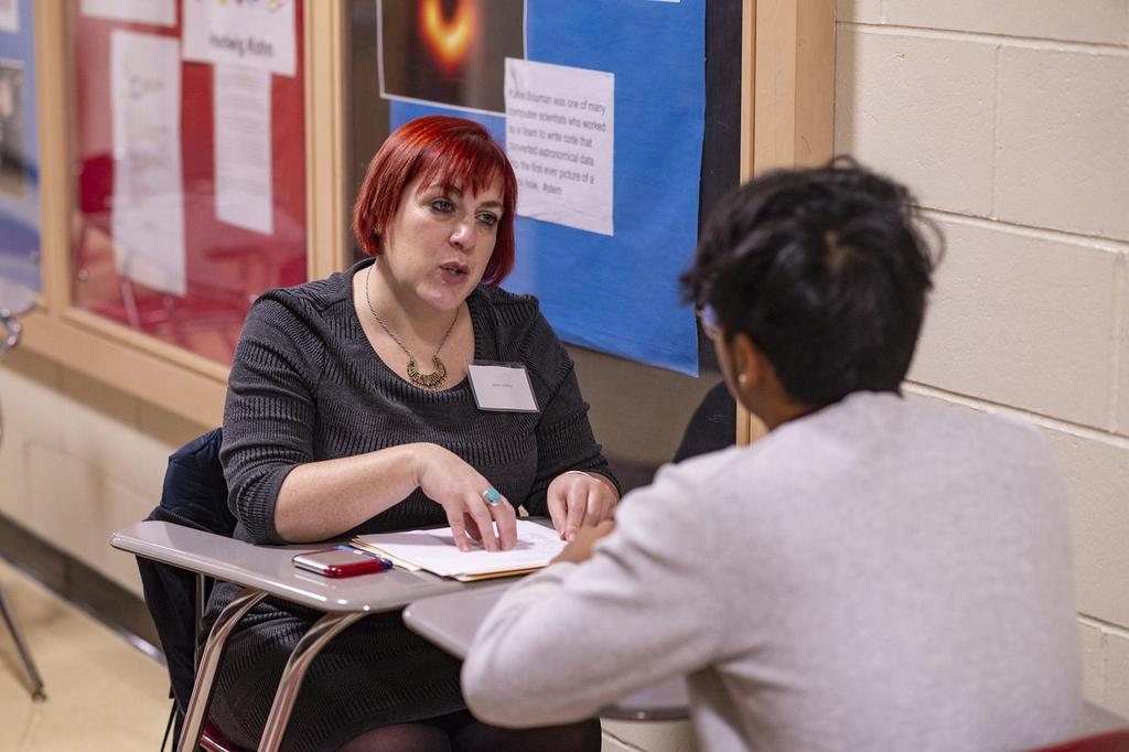 Jamie Lederer indicates something on a piece of paper as she interviews a student