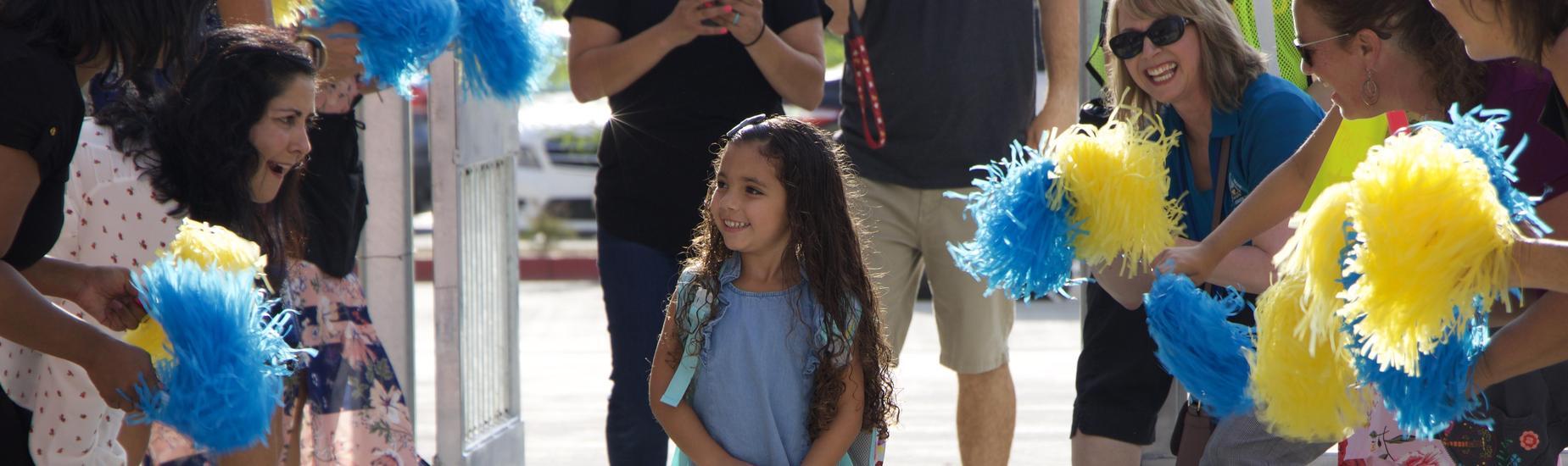 Little Girl Walking. Teachers cheering with pom poms