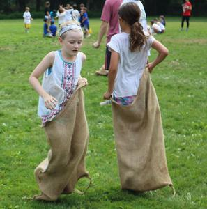 Students at Washington School enjoy sack races during Field Day.