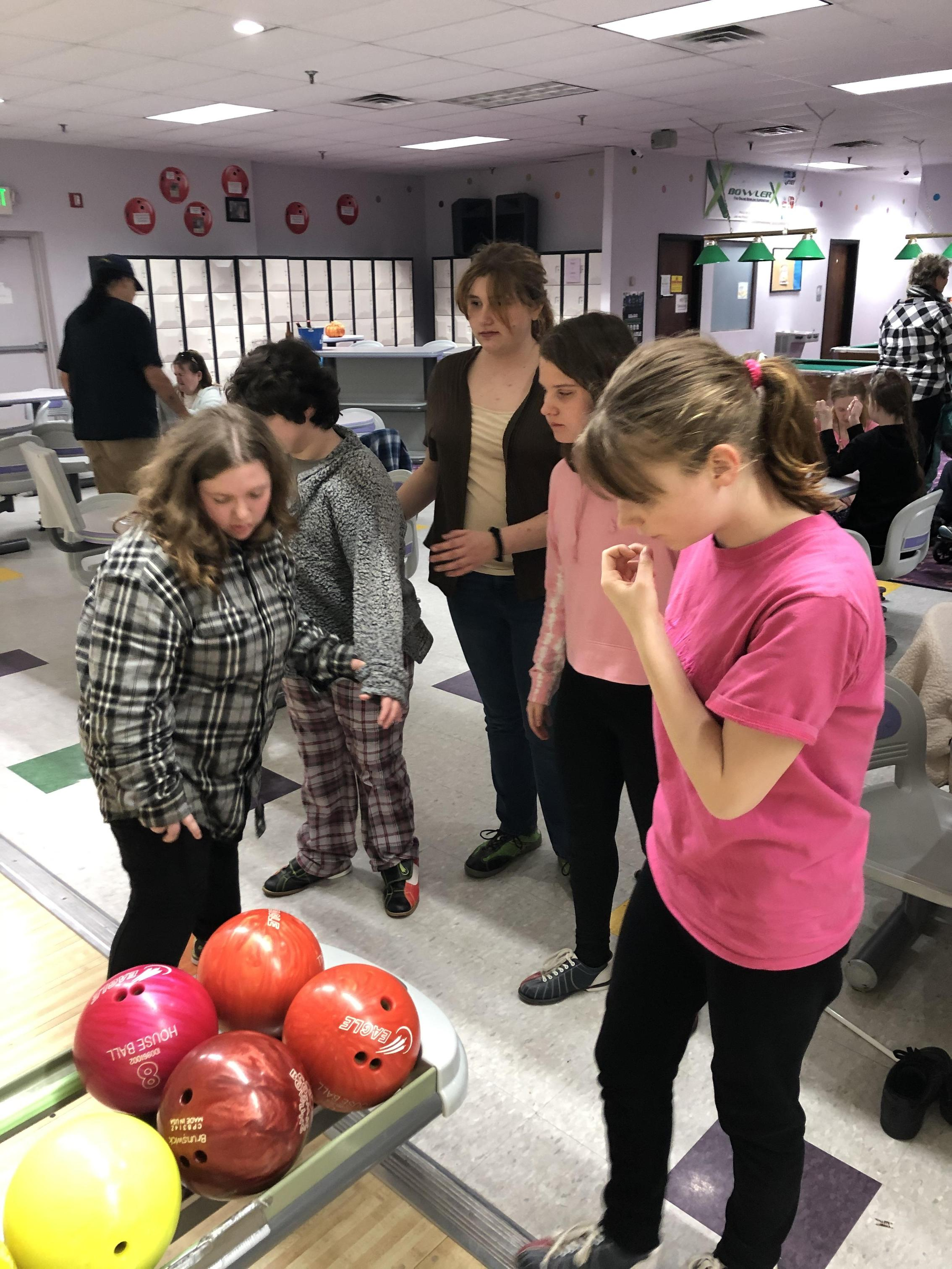 Students standing together around the Bowling ball return