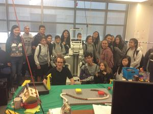 students and presenters standing around a metal robot that is human sized
