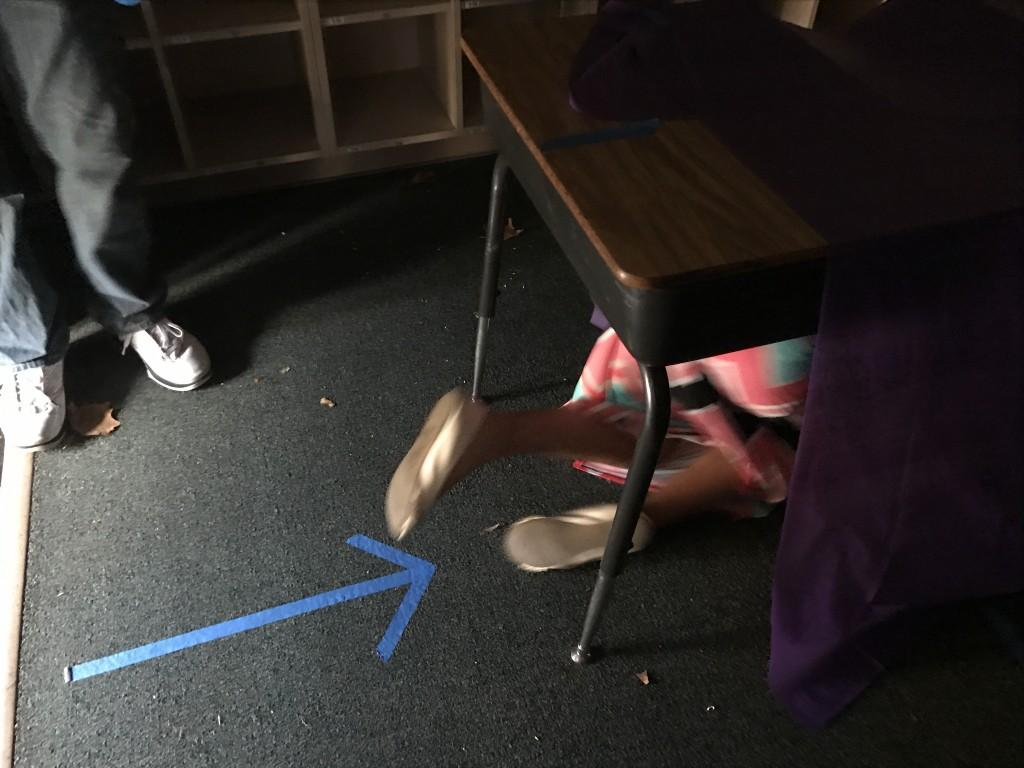 Student crawling under desk