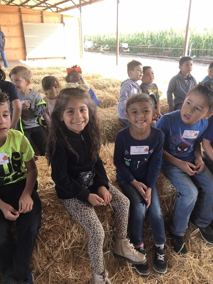 students smiling while sitting on hay bales