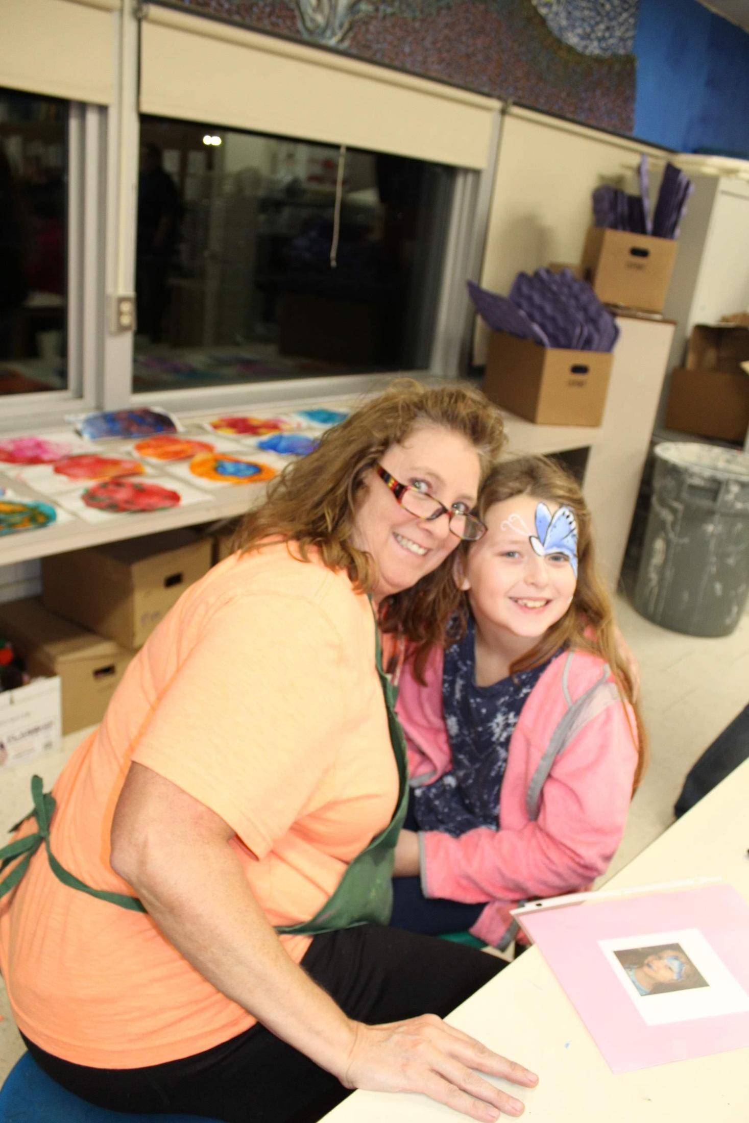 Art teacher and student with face painting.