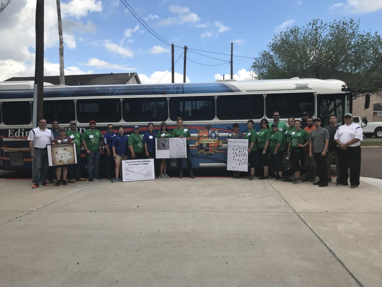 Group of teachers pose outside of bus holding information posters