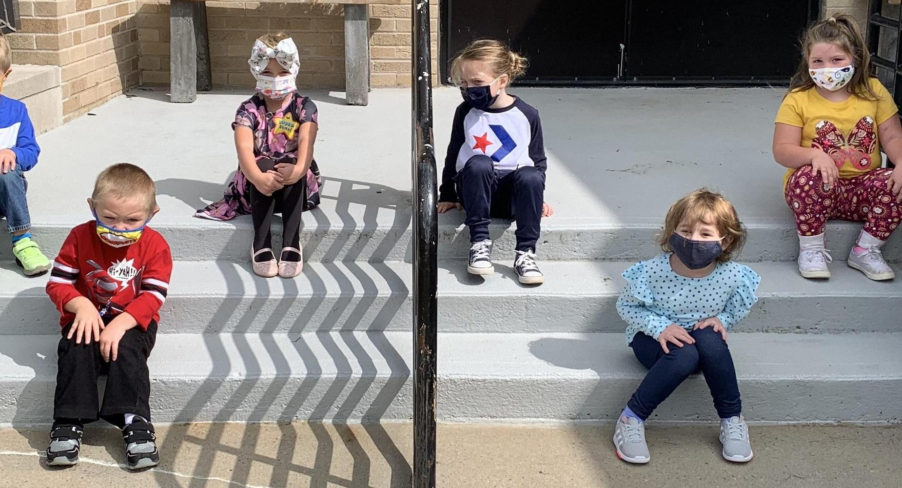 students seated on steps posing for picture