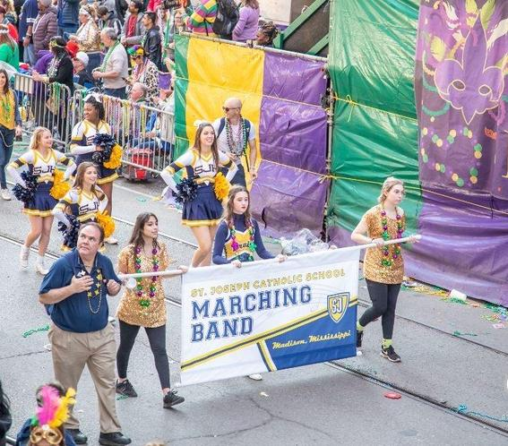 high school marching band holding banner that says